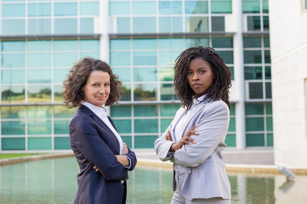 Succesvolle vrouwelijke mix racete zakelijke partners die buiten poseren Gratis Foto