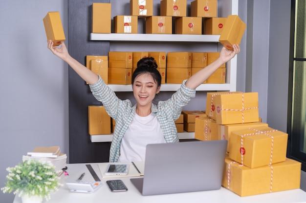 Succesvolle vrouwenondernemer met pakketdozen in haar eigen baan die online zaken winkelt Premium Foto