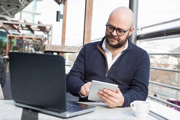 Succesvolle zakenman blijft werken tijdens koffiepauze Gratis Foto