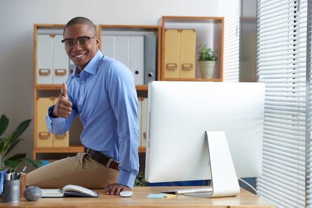 Succesvolle zakenman die duimen tonen en glimlachen die op zijn werkend bureau neerstrijken Gratis Foto