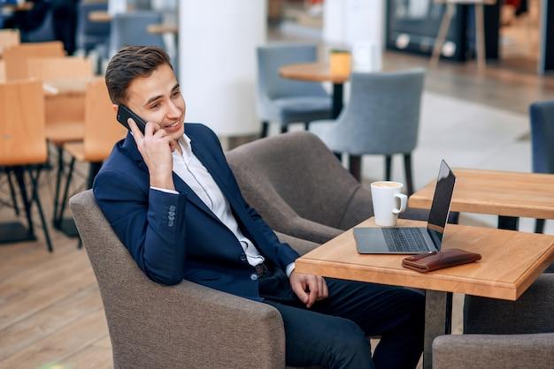 Succesvolle zakenman die op smartphone op zijn werkplaats met laptop, portefeuille en notitieboekje spreekt Premium Foto