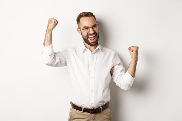 Succesvolle zakenman die zich verheugt, handen opheft en overwinning viert, iets wint Gratis Foto