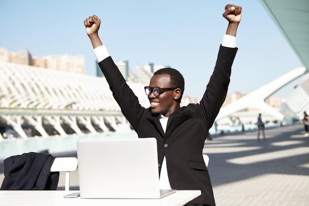 Succesvolle zakenman die zijn handen opheft die vrolijke uitdrukking hebben na ondertekening van contract Gratis Foto
