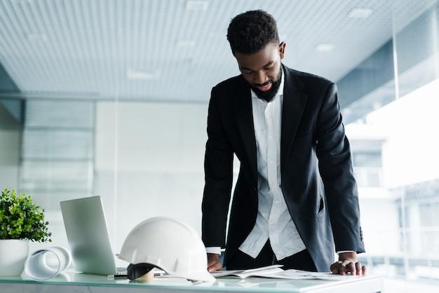 Succesvolle zakenman. knappe jonge afrikaanse man die zich in creatief bureau bevindt Gratis Foto