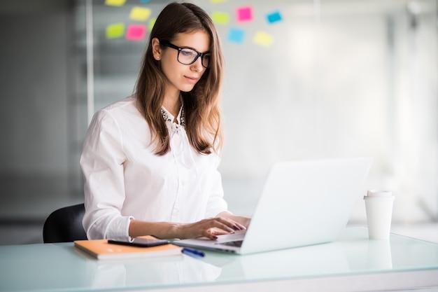 Succesvolle zakenvrouw die op laptopcomputer in haar kantoor werkt, gekleed in witte kleren Gratis Foto
