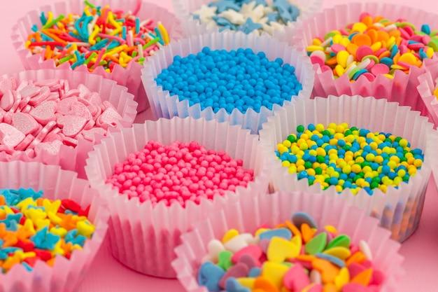 Suiker hagelslag, decoratie voor cake en ijs en koekjes op roze achtergrond Premium Foto