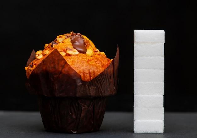 Suikerniveau naast de cupcake, kubussen suiker op elkaar gestapeld, de hoeveelheid suiker in de schaal Premium Foto