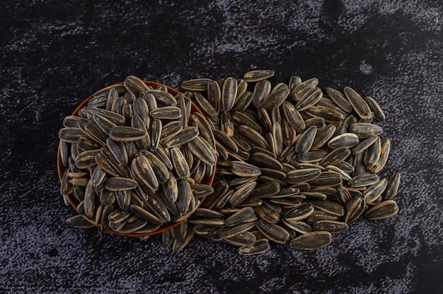 Sun flower-zaad in een houten kom op de zwarte cementvloer. Gratis Foto