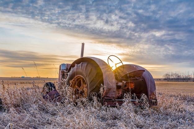 Sunburst bij zonsondergang over een vintage tractor verlaten in hoog gras op de prairies in saskatchewan Premium Foto