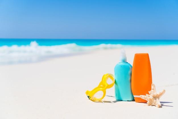 Suncream-flessen, bril, zeester op wit zandstrand met uitzicht op de oceaan Premium Foto