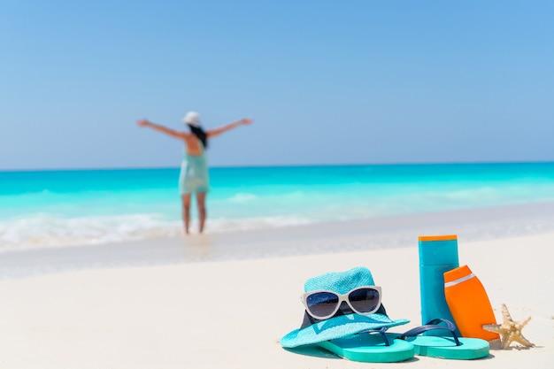 Suncream-flessen, zonnebril, wipschakelaar op wit zand Premium Foto