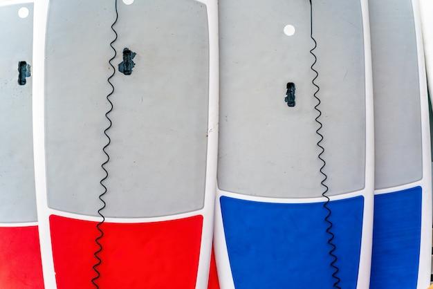 Sup board verhuur plaats op het strand. surfplanken, veel verschillende surfplanken op het strand, watersport, vrolijke actieve zomervakantie. rij stand-up paddle-planken klaar om te huren. Premium Foto