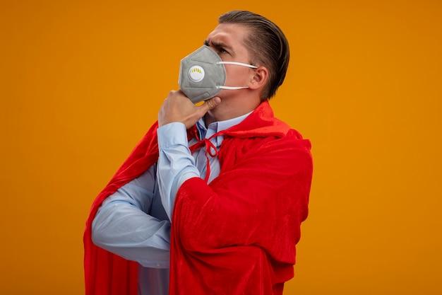 Super held zakenman in beschermend gezichtsmasker en rode cape opzij kijken met hand op kin denken met serieuze blik staande over oranje achtergrond Gratis Foto