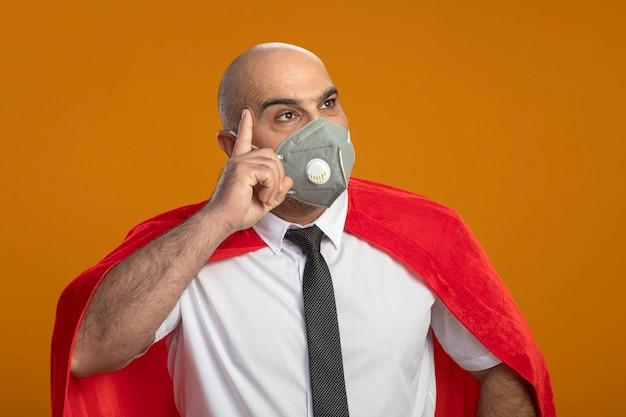 Super held zakenman in beschermend gezichtsmasker en rode cape opzij kijken met peinzende uitdrukking op gezicht denken Gratis Foto