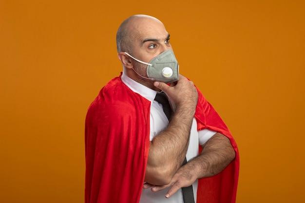 Super held zakenman in beschermend gezichtsmasker en rode cape opzij kijken met peinzende uitdrukking op gezicht met hand op kin denken Gratis Foto
