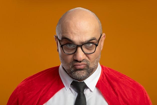 Super held zakenman in rode cape en bril camera kijken met fronsend gezicht ontevreden Gratis Foto