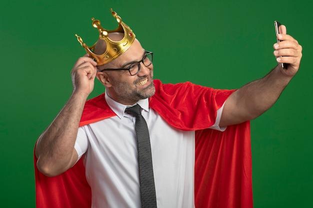 Super held zakenman in rode cape en bril dragen kroon doen selfie met smartphone glimlachen Gratis Foto
