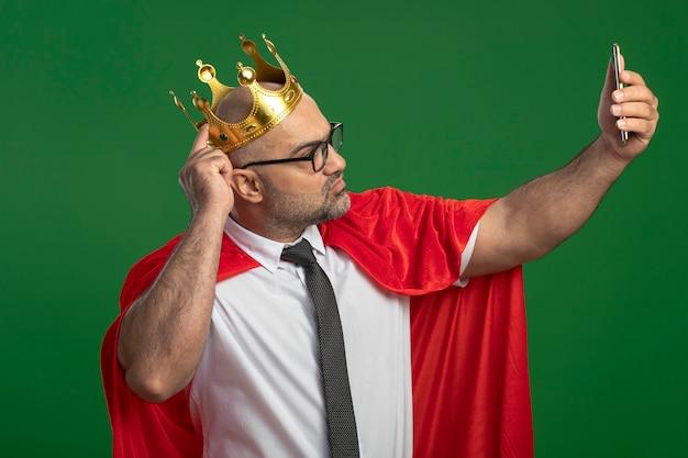 Super held zakenman in rode cape en bril dragen kroon doen selfie met smartphone Gratis Foto