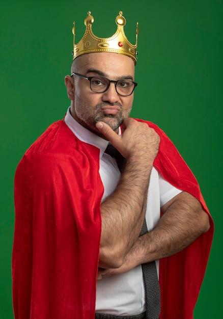 Super held zakenman in rode cape en bril dragen kroon met hand op kin met zelfverzekerde ernstige uitdrukking Gratis Foto