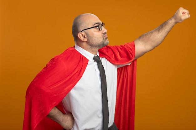 Super held zakenman in rode cape en bril opzij kijken arm in vliegende gebaar klaar om te helpen Gratis Foto