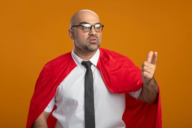 Super held zakenman in rode cape en bril opzij kijken verward wijzend op iets met index figner Gratis Foto
