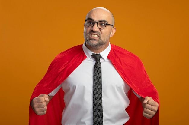 Super held zakenman in rode cape en glazen balde vuisten boos en gefrustreerd Gratis Foto