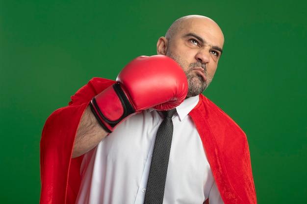 Super held zakenman in rode cape en in bokshandschoenen zichzelf ponsen Gratis Foto