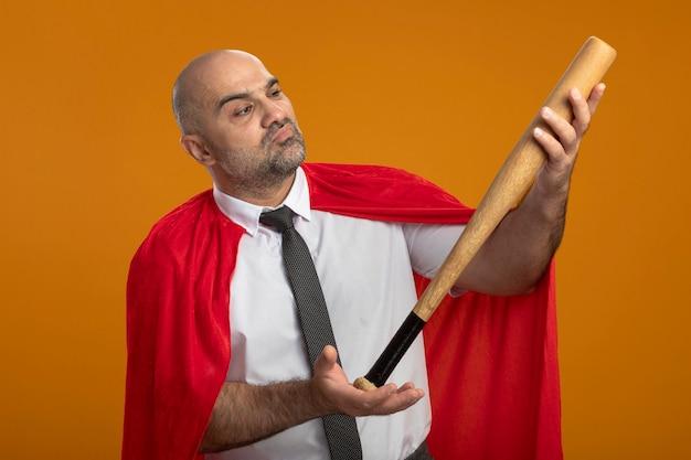 Super held zakenman in rode cape houden honkbalknuppel kijken geïntrigeerd Gratis Foto