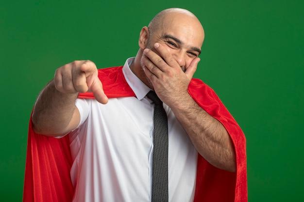 Super held zakenman in rode cape lachen bedekkend mond met hand wijzend met index figner op camera Gratis Foto