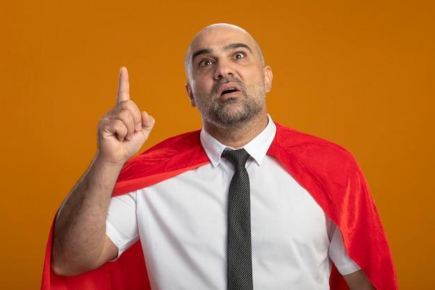 Super held zakenman in rode cape loking tonen index figner wordt verrast met nieuw idee Gratis Foto