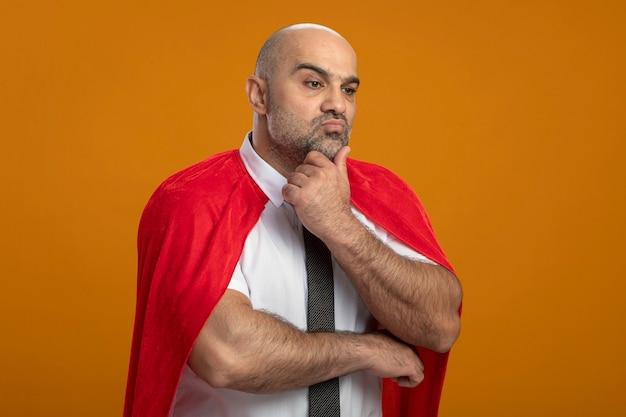 Super held zakenman in rode cape opzij kijken met peinzende uitdrukking op gezicht denken Gratis Foto