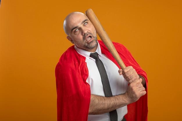 Super held zakenman in rode cape ponsen zichzelf met honkbalknuppel Gratis Foto