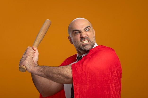 Super held zakenman in rode cape swingende honkbalknuppel met boze agressieve uitdrukking wild gaan Gratis Foto