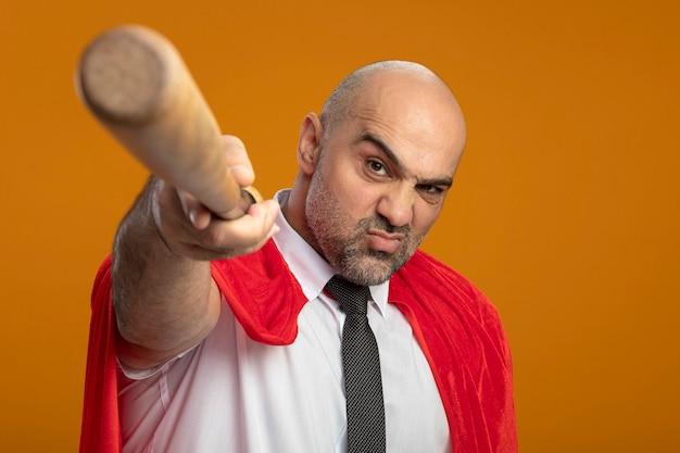 Super held zakenman in rode cape wijzend met honkbalknuppel camera kijken met boos gezicht Gratis Foto