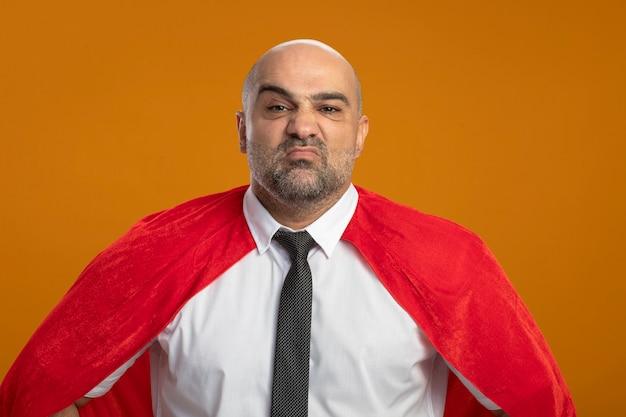 Super heldzakenman die in rode cape voorzijde bekijken die zich over oranje muur ontevreden bevinden Gratis Foto