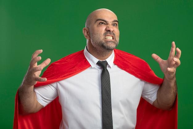 Super heldzakenman in rode cape die wild opheft handen met agressieve uitdrukking die zich over groene muur bevindt Gratis Foto