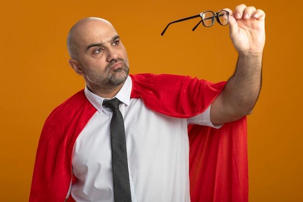 Super heldzakenman in rode cape die zijn bril houdt die hen met ernstig gezicht bekijkt Gratis Foto