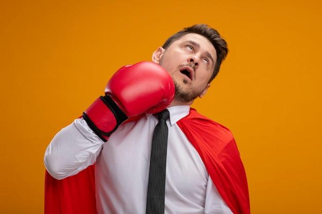 Super heldzakenman in rode kaap en in bokshandschoenen die zich over oranje muur ponsen Gratis Foto