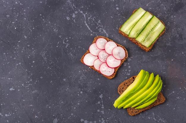Superfood open vegetarische sandwich met verschillende toppings: avocado, komkommer, radijs op donkere achtergrond. gezond eten. biologisch en vegetarisch eten. plat lag, kopieer ruimte voor tekst, minimalisme Premium Foto
