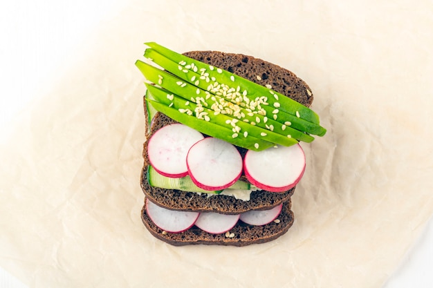 Superfood open vegetarische sandwich met verschillende toppings: avocado, komkommer, radijs op papier op witte achtergrond. gezond eten. biologisch en vegetarisch eten. close-up, kopieer ruimte voor tekst Premium Foto