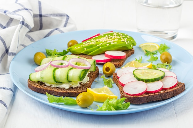 Superfood open vegetarische sandwich met verschillende toppings: avocado, komkommer, radijs op plaat en glas water op witte achtergrond. gezond eten. biologische en vegetarische foodr tekst Premium Foto