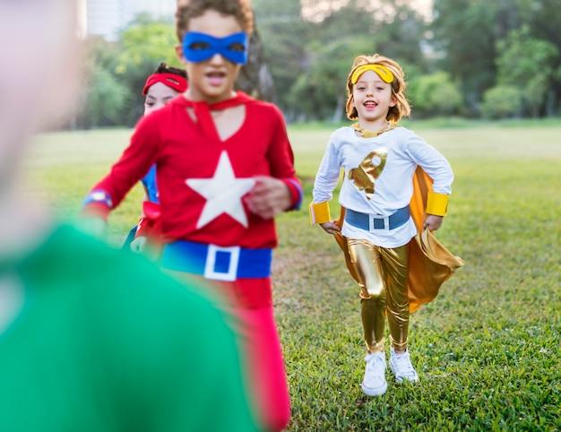 Superhelden vrolijke jonge geitjes die positiviteitsconcept uitdrukken Premium Foto