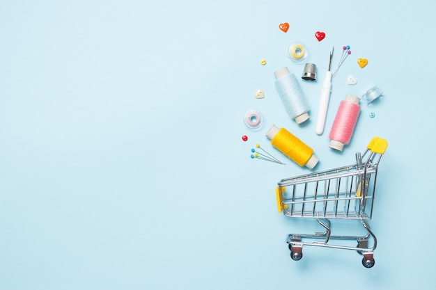 Supermarktkar met naaien accessoires op blauwe achtergrond, stiksels, borduurwerk. Premium Foto