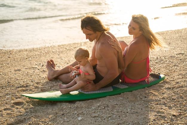 Surfen. gelukkige familie zit op de surfplank. concept over familie, sport en plezier Premium Foto