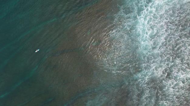 Surfen vanuit de lucht, luchtfoto bovenaanzicht van strand met oceaan golven op bali Premium Foto