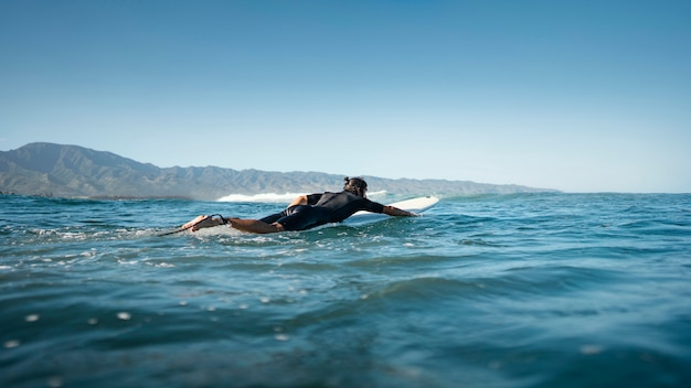 Surfer die in het afstandsschot van het water zwemt Gratis Foto