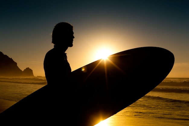 Surfer en board in avondzon Premium Foto