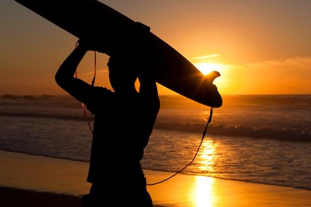 Surfer en board in avondzon Premium Foto