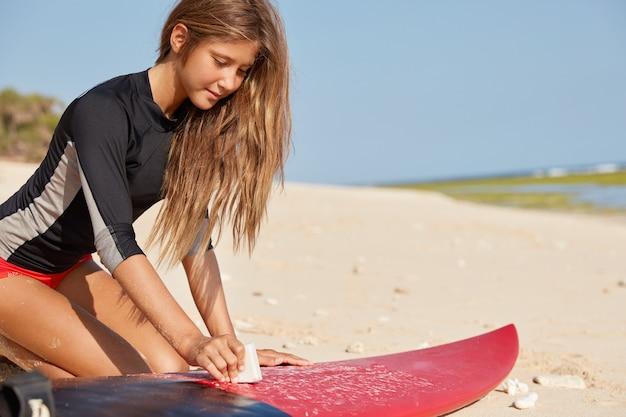 Surfer en oceaan. bijgesneden afbeelding van actieve meisje gekleed in badpak, zit op warm zand Gratis Foto