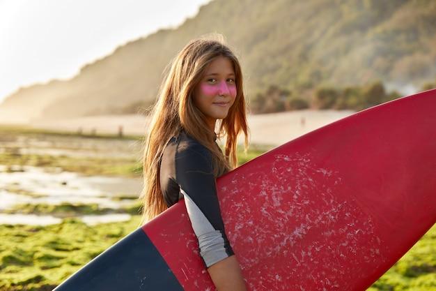 Surfer en oceaan concept. opgetogen donkerharige vrouw draagt gewaxte surfplank-looks met tevreden uitdrukking Gratis Foto